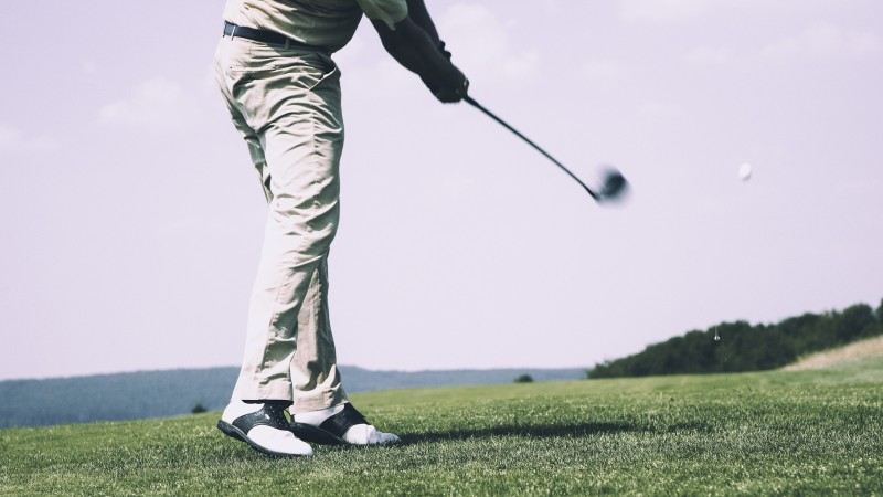 Man swings a golf club iron