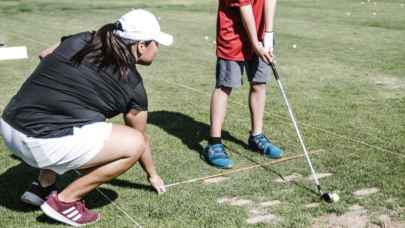 Are Golf Lessons Worth the Money? This kid is playing golf with his instructor