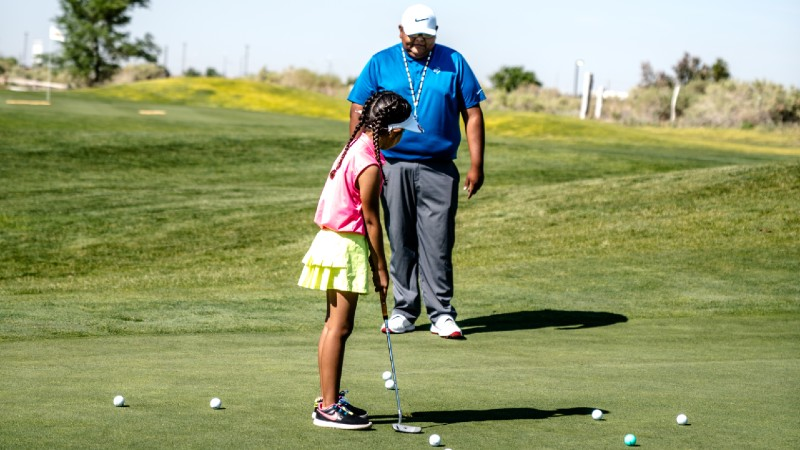 girl taking part in a one on one golf lesson with a qualified golf coach