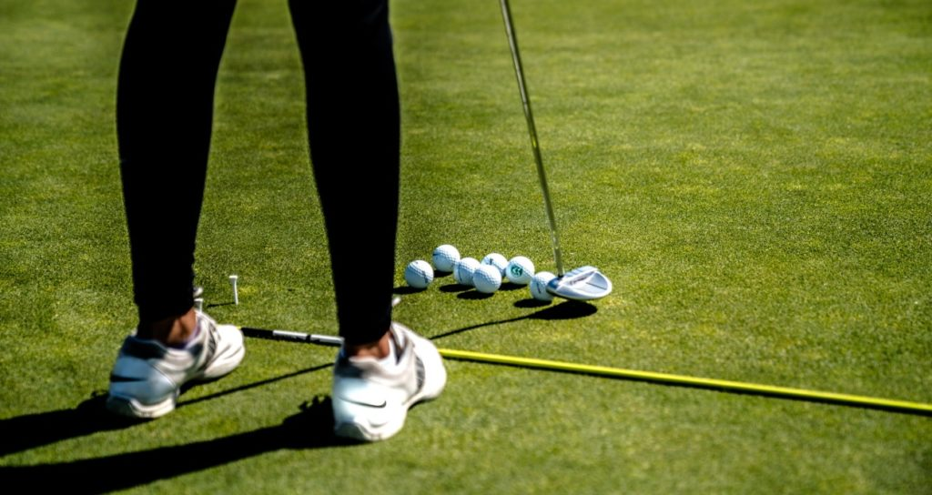 Girl practising putting on the green