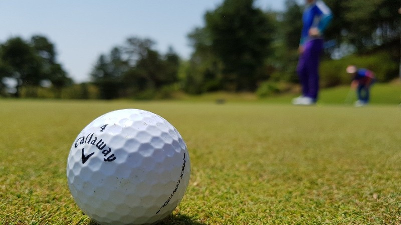 Close up of a golf ball while the golfer is reading the green before putting