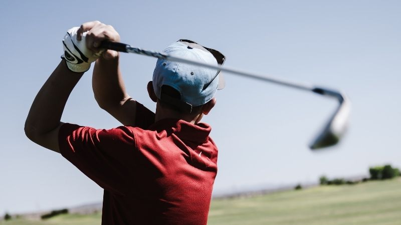 hitting an iron on the golf course