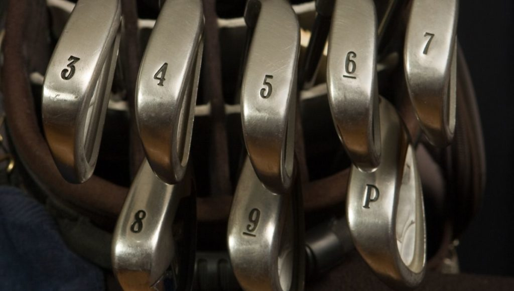 A set of irons with a steel shaft in a golf bag