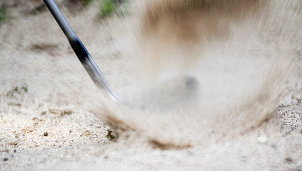 A sand wedge hitting a golf ball out of a bunker