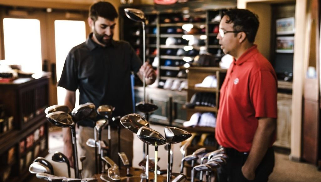Two men looking at golf clubs in a shop discussing Graphite vs Steel Golf Clubs