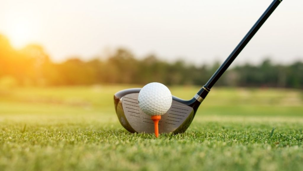 A golf driver behind a golf ball on a tee