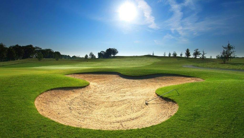 A freshly raked bunker on a golf course. Avoid these with a strong mental game and choosing the right shots.
