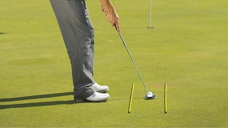 A man showing How To Use Alignment Sticks In Golf when putting