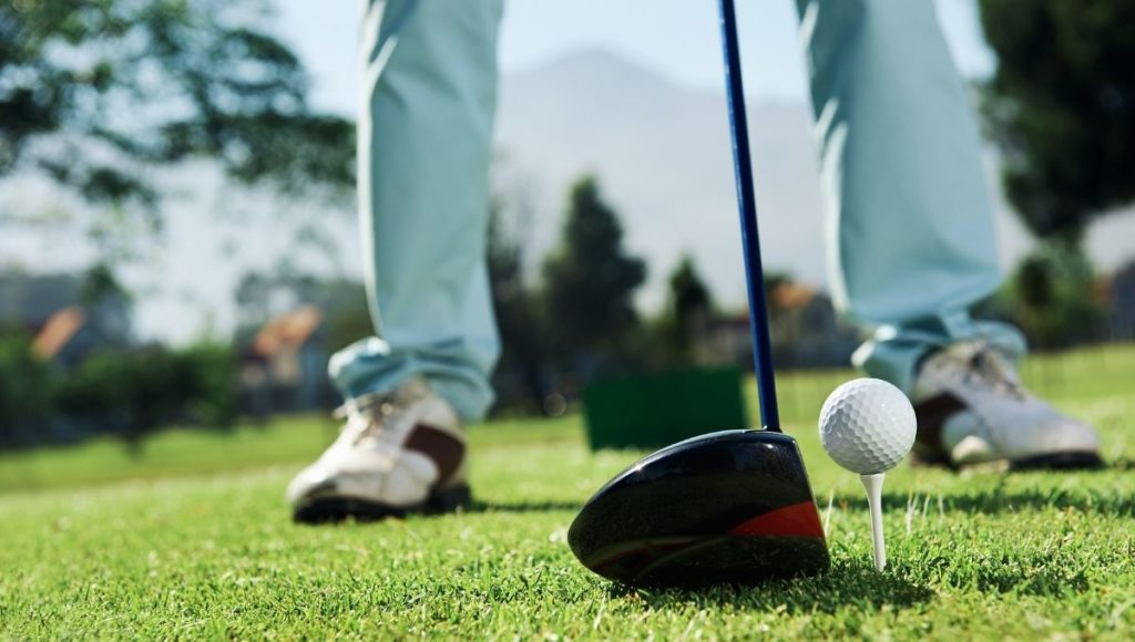 A man getting ready to drive a golf ball off the tee