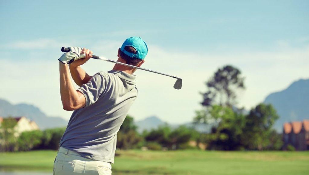 Man taking a golf shot with an iron