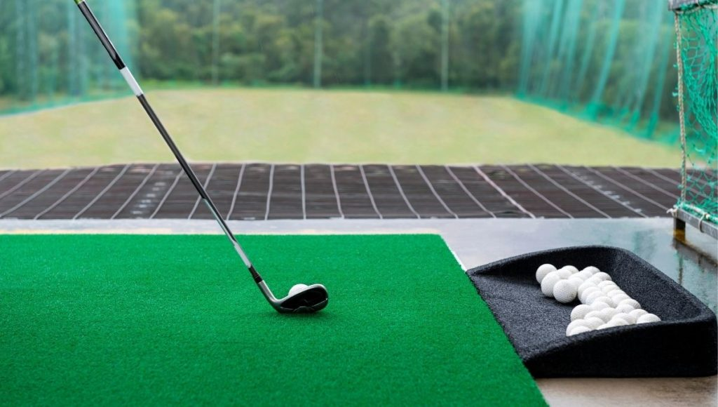 Someone at a golf driving range practicing with their irons and a portable launch monitor