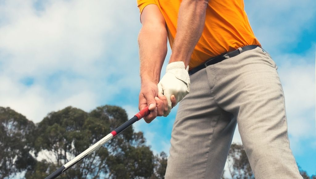 A man ready to hit the golf ball with a golf stick