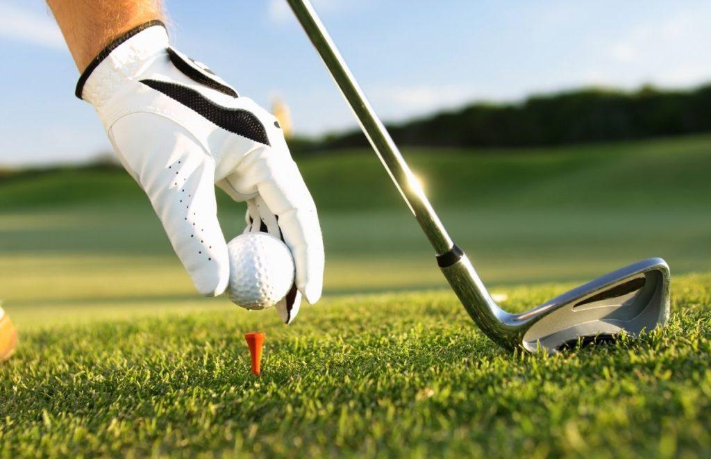 A man wearing a golf glove putting a ball on a tee