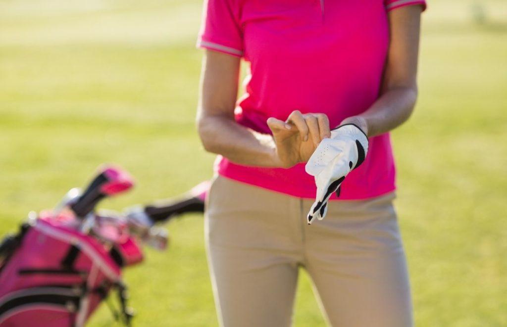 A lady golfer putting on a golf glove