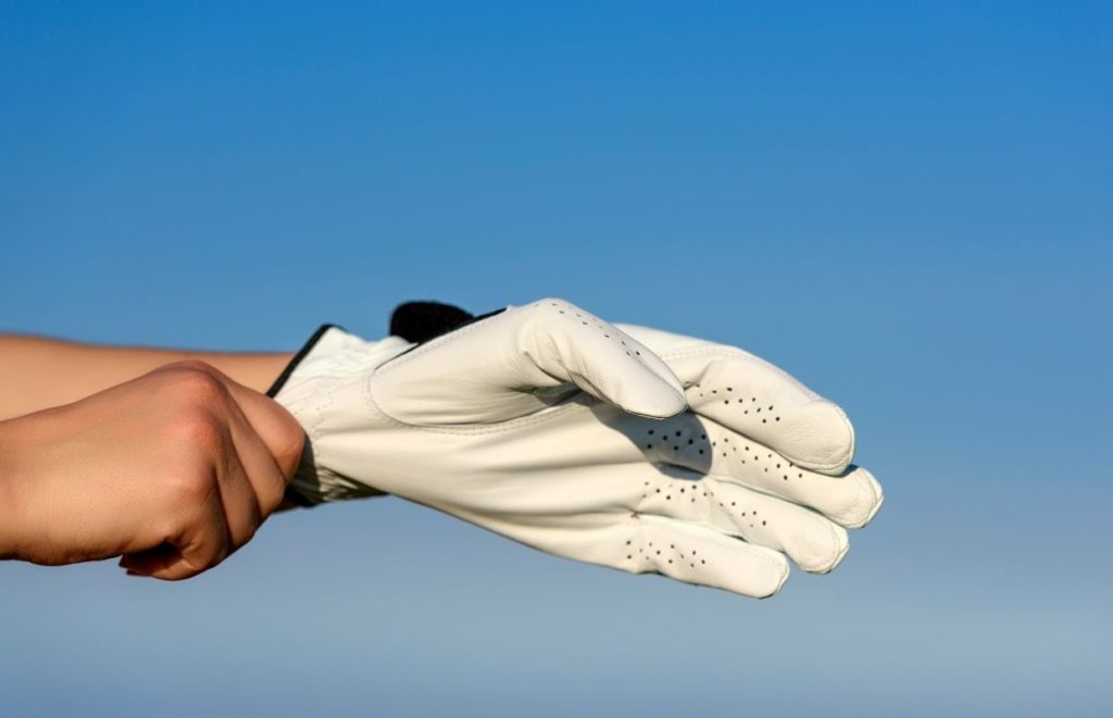 A person putting on the Best Golf Gloves that have a perfect fit